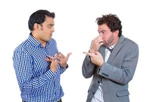 Was tun gegen Schweißfüße im Büro! Zwei Männer beschuldigen sich gegenseitig nach Käsefüße zu stinken.